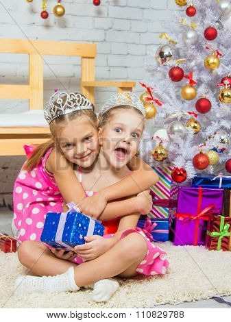 Girl Hugging Another Girl Sitting On A Rug With A Gift At Christmas Tree