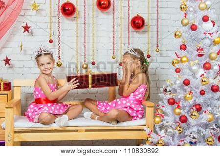 Girl Gives Another Girl A Gift Sitting On A Bench In A Christmas Setting
