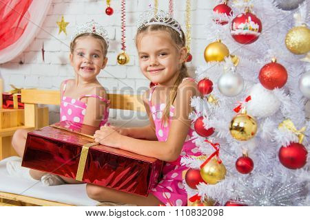 Two Happy Girls Sitting On A Bench With A Christmas Present