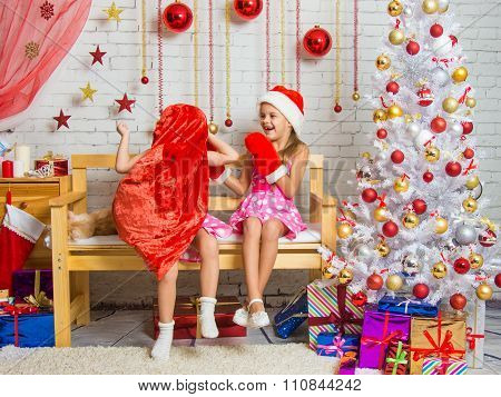 Girl In A Cap And Mittens Of Santa Claus Laughing At The Girl Who Put A Sack On His Head