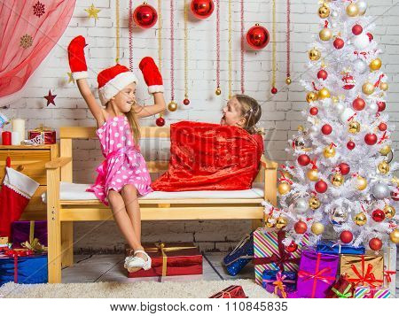 Girl In A Cap And Mittens Of Santa Claus Surprised That A Girl Got Out Of The Bag