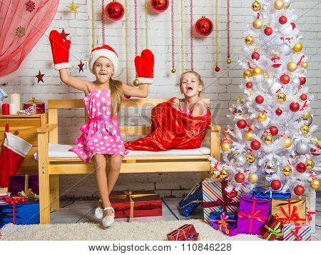 On The Bench Sits A Girl In A Cap And Mittens Of Santa Claus, The Other Girl With A Laugh Comes Out