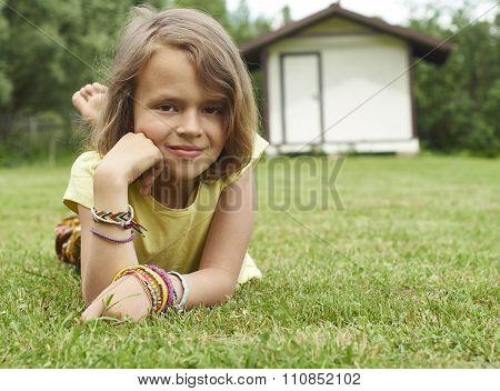 Portrait of girl of ten lying on green grass.