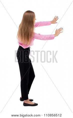 back view of business woman pushes wall.  Isolated over white background. Blond girl in green skirt pushing something heavy right. girl office worker in black trousers shoves something in front of him