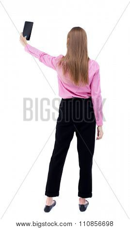 back view of standing young beautiful  girl with tablet computer in the hands of. girl  watching.  Isolated over white background. The girl office worker in black trousers aloft smartphone makes self.