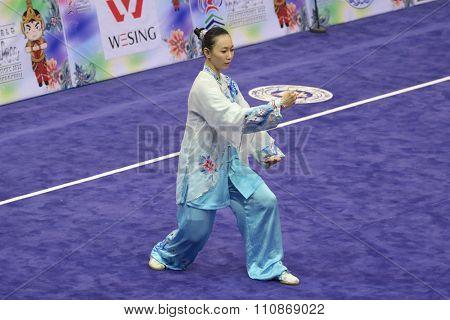 JAKARTA, INDONESIA: NOVEMBER 14, 2015: Shin Ng from Malaysia performs the movements in the women's Taijiquan event at the 13th World Wushu Championship 2015 at Istoran Senayan.