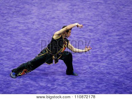 JAKARTA, INDONESIA, NOVEMBER 14, 2015: Sami Ben Mahmoud from Switzerland performs the movements in the men's Nanquan event at the 13th World Wushu Championship 2015 held in Istora Senayan, Jakarta.