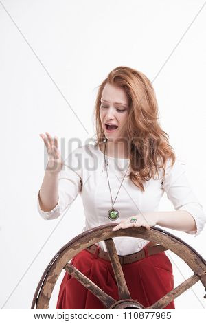 young woman with an old wagon wheel on white background