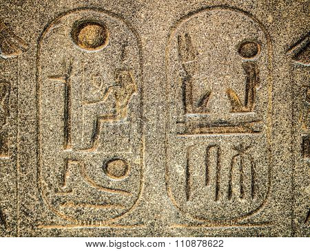 Ancient egyptian hieroglyph carved in stone  with cartouches enclosing royal names