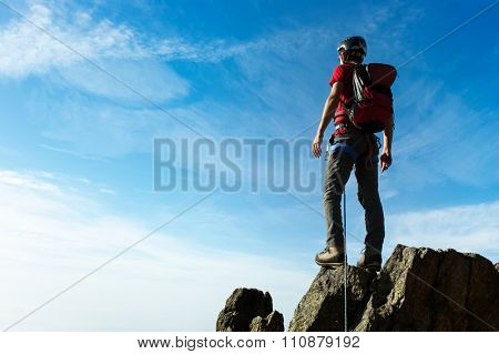 Climber arrive on the summit of a mountain peak. Concepts: victory, success, achievement, triumph.