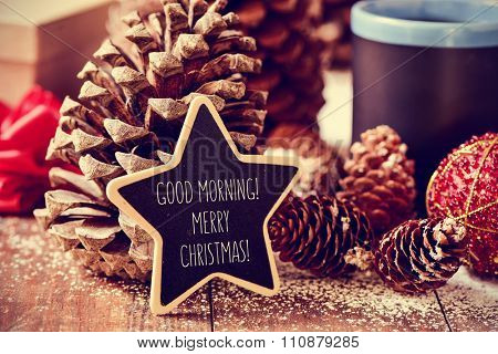 the text good morning merry christmas written in a star-shaped blackboard on a rustic wooden surface with some pinecones, a red christmas bauble and a mug with tea or coffee
