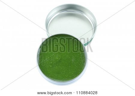 A small balm jar full of medicated ointment in green color, isolated on white