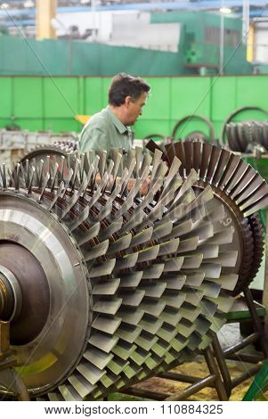 Mechanic works with parts of aviation engine