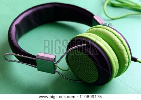 A pair of modern headphones, on green background