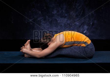 Sporty fit woman practices Ashtanga Vinyasa yoga back bending asana Paschimottanasana - seated forward bend
