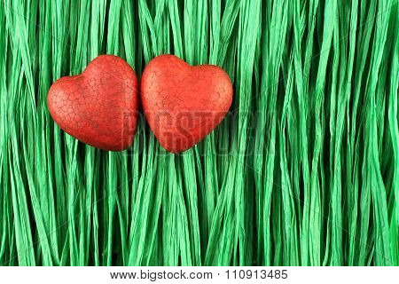 Two red painted polyfoam hearts on green paper raffia strips background