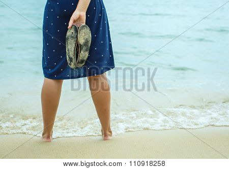Woman Standing On The Beach And Holding In His Hand Spanking
