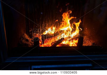 heating, warmth, fire and cosiness concept - close up of burning fireplace at home