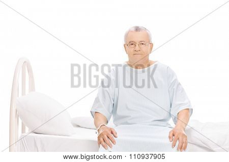Senior patient in a hospital gown sitting on a bed and looking at the camera isolated on white background