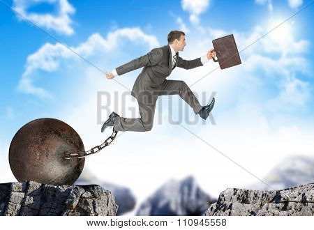 Businessman with suitcase and iron ballast  hopping over bottomless pit poster