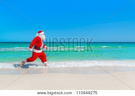 Christmas Santa Claus Running At Tropical Beach On Waves Splashes