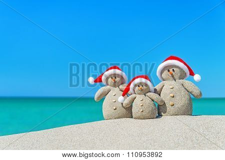 Family Of Snowmen In Santa Hats At Tropical Beach. Christmas Concept.