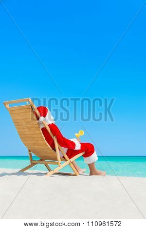 Christmas Santa Claus Drinking Cocktail On Sunlounger At Tropical Beach