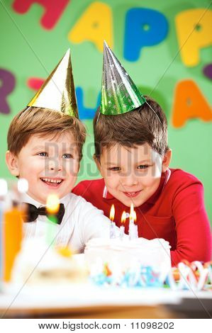 Portrait of happy boys on birthday party with cake near by poster