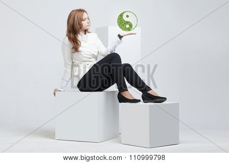 Young woman holding green plant ying yang symbol poster