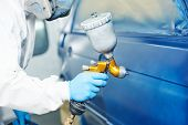 automobile repairman painter hand in protective glove with airbrush pulverizer painting car body in paint chamber poster