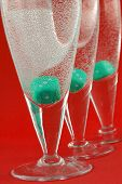 glasses on the red background with green dices in it poster