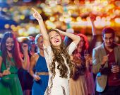 people, holidays and nightlife concept - happy young woman or teen girl in fancy dress with sequins and long wavy hair dancing at night club party over crowd and lights background poster