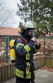 Firefighter with breathing apparatus and oxygen cylinder in action poster
