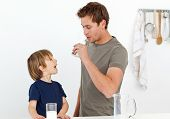 Happy dad and son drinking milk together in the kitchen poster