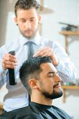 Like to be handsome. Selective focus of content pleasant man sitting in the barber shop while professional barber making him a  hairstyle poster