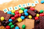 Heap of sweet candies and cookies with brown cane sugar and word diabetes unhealthy food concept of diabetes and reduction of eating sweets poster