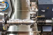 metalworking  industry: cutting steel metal shaft processing on lathe machine in workshop. Selective focus on tool poster