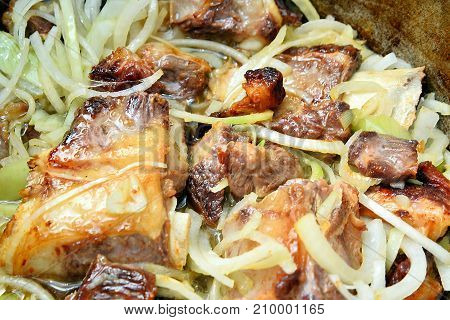 fried meat onions beef meat in a cauldron cooking animal fat vegetable oil