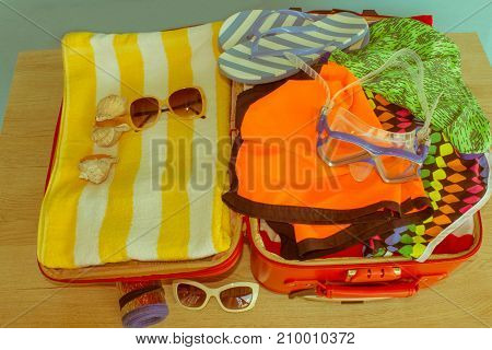 Travel and vacations concept. Open traveler's bag with clothing accessories. Open suitcase with different things - Retro color
