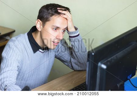 Despaired boy in front of the computer