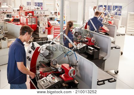 Trainee engineers operating equipment in a small factory