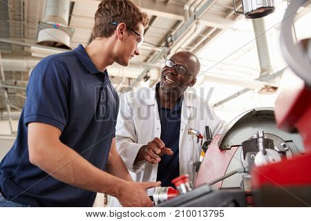 Engineer talking to male apprentice at his workstation, low angle