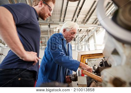 Senior engineer demonstrating equipment to apprentice at machine bench, low angle