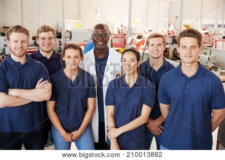 Engineer with apprentices in factory, group portrait