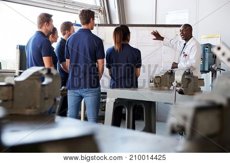 Engineering apprentices watching presentation at whiteboard