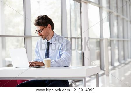 Young businessman at a desk working on his laptop