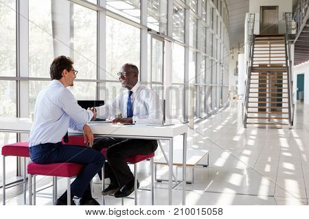 Two businessman shake hands during a meeting