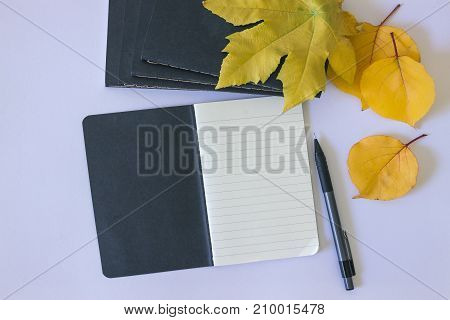 Black notepad for notes and yellow leaves on a white background. Concept- autumn creative mood and comfort.