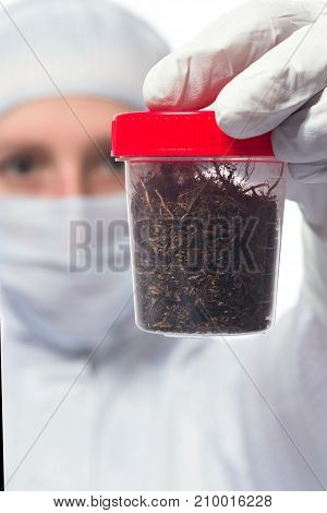 the hand of the scientist in a special suit holding a jar of samples of earth for analysis