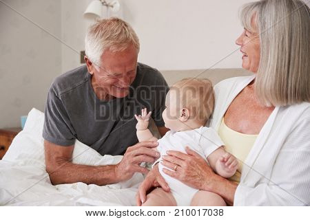 Grandparents Lying In Bed At Home Looking After Baby Grandson poster